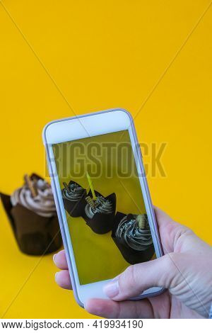Female Hands Taking Photo Of Delicious Chocolate Cupcakes With Cream On Yellow Background. Influence