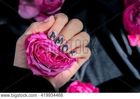Amor Word On Nails Manicure Hold Pink Rose Flower On Black Silk Fabric. Minimal Flat Lay Nature. Fem