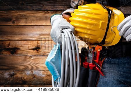 Electrician Technician With Tool Belt And Surgical Mask On Rustic Wooden Background. Electricity. Co