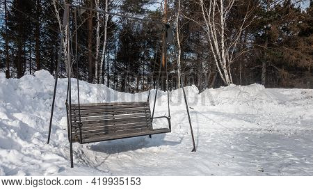 Wooden Swing In The Form Of A Bench On Metal Supports. Around, In The Park, Snowdrifts. In The Backg
