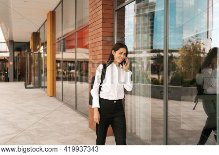 Woman With Business Backpack Walking While Speaking On The Phone Near A Business Building