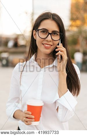 Corporate Communication. Caucasian Businesswoman In Eyewear Talking On Mobile Phone With Coffee To G
