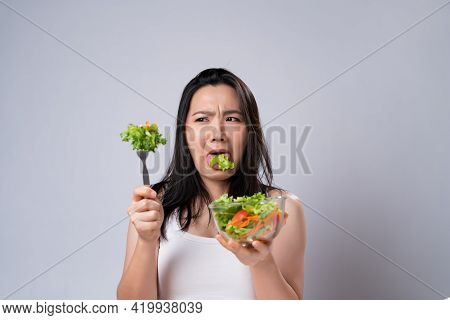 Asian Woman Trying To Eat Salad For Diet Isolated Over White Background.