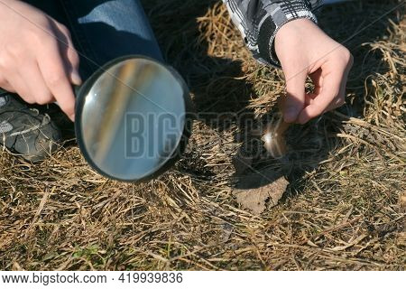Hand Of A Boy With A Magnifying Glass Who Is Trying To Set Fire To The Grass On The Street. Children