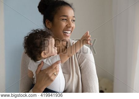 Overjoyed Young Ethnic Mom Cuddle Little Baby Daughter