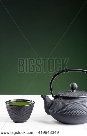 Green Tea And Teapot On Green Background On White Wooden Base With Copyspace. Traditional Japanese D