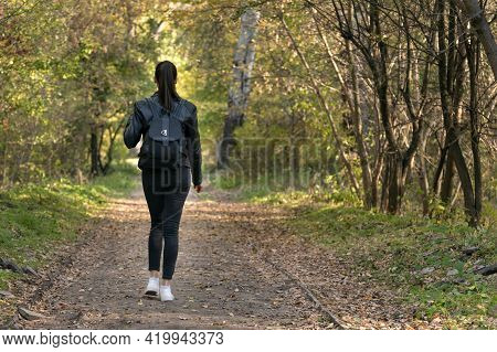 Young Woman Is Walking Along The Autumn Alley Of The Park. Back View.