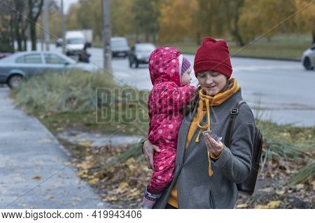 Mom Walks Down The Street With Toddler In Her Arms. Nanny And Child On The Street