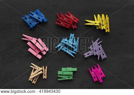 Clothespins Of Different Colors Are Divided Into Groups. Sets Of Bright Clothespins On Black Backgro