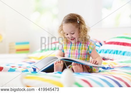 Child Reading Book In Bed In White Sunny Bedroom With Window. Kids Read Books. Bedding And Textile F