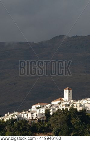 View Of The White Village Of Capileira In The Alpujarra Region With The Sierra Nevada Mountains In T