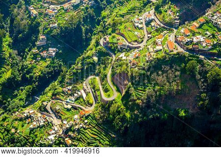 Road Serpentines On The Island Of Madeira. A Long Mountain Winding Road Between Family Houses And Fi