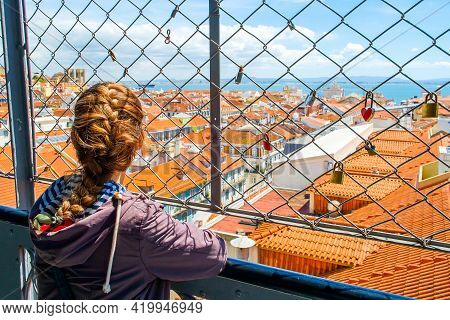 Beautiful View From The Center Of The Portuguese City Of Lisbon With A Young Girl In The Foreground.