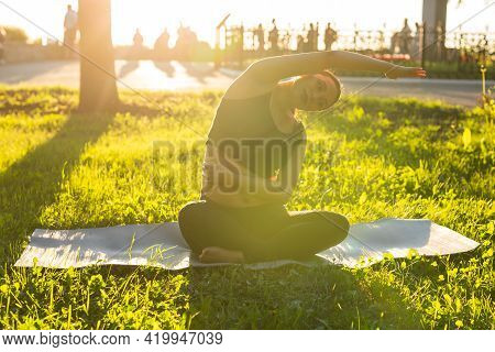Peaceful Young Positive Pregnant Woman In Gymnastic Suit Does Yoga And Meditate Sitting On Mat On Gr