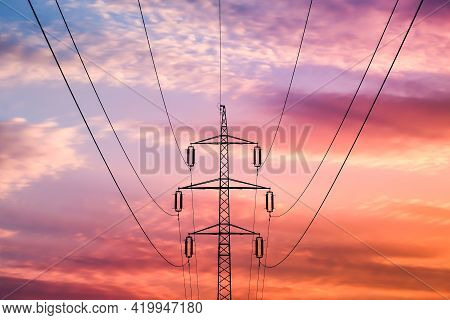 High Voltage Pylon At Sunset. Power And Energy. Photos On The Theme Of Electricity.