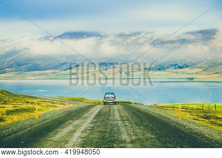 Car On The Road. Roadtrip In Iceland. In The Foreground Is A Road And The Car, In The Background Is