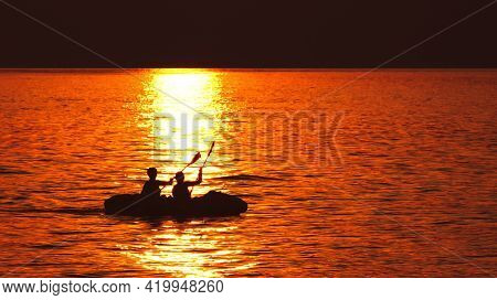 Persons Paddling In Boat On Sea At Sunset. Summer Recreation By The Sea.