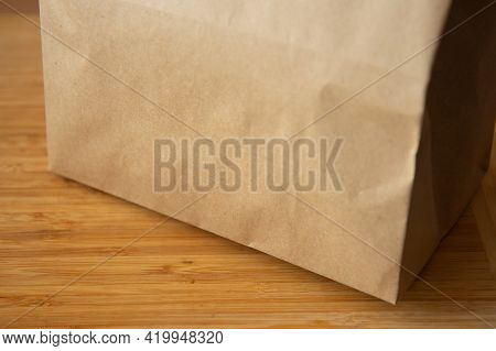Brown Craft Paper Bag On Light Wooden Background. Recycled Paper Shopping Bag, Lunch Bag