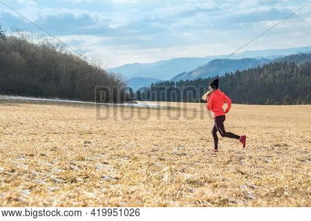 Athlete woman runs in the spring forest. Young female runner jogging exercise outdoors in the morning. Workout for marathon and fitness.