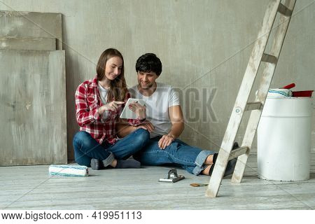 Family Couple Using Digital Tablet During Renovation In New House. Young Couple Sits On The Floor An