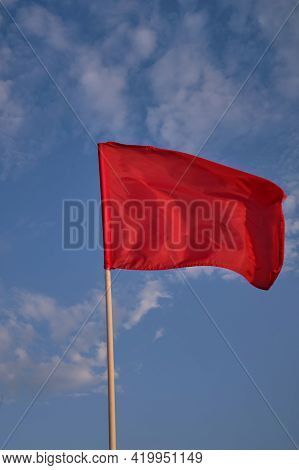Red Flag With Blue Sky With Clouds, Strong Wind Flying Red Flag. Red Flag Warning Flags