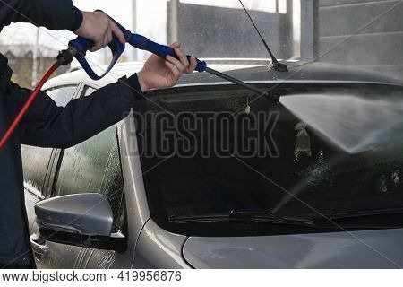 A Worker Washes The Windshield Of A Gray Car With A Jet Of Water From A High-pressure Car Wash At A