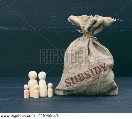Wooden Figures Of Little Men Of A Family And A Full Bag With The Inscription Subsidy On A Blue Backg