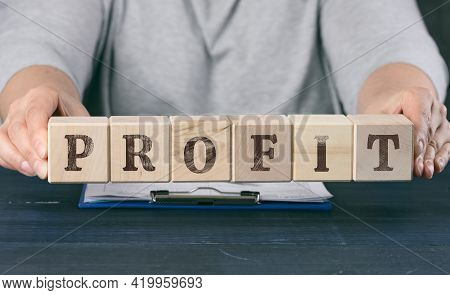 Two Female Hands Hold Wooden Cubes With The Inscription Profit. Business Growth, Easy Money. Profita