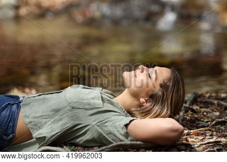 Profile Of A Happy Woman Relaxing Resting Lying In A Riverside