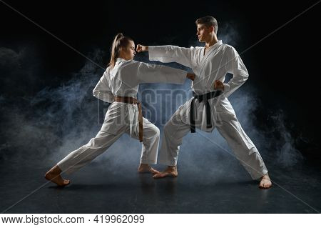 Female karate fighter on training with master