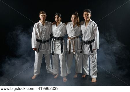 Four karate fighters in white kimono poses in hug