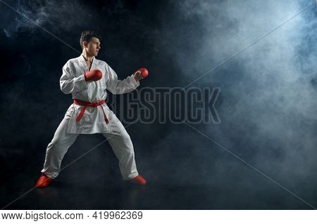 Male karate fighter in white kimono and red gloves