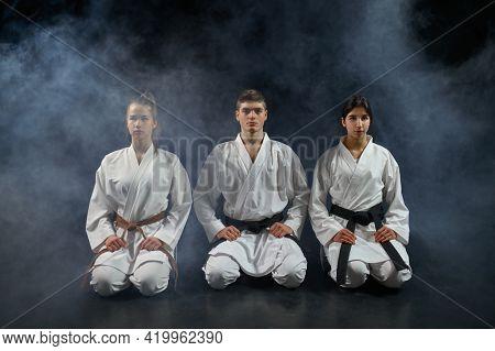 Female karate fighters and master in white kimono
