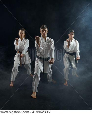 Male and female karate fighters in white kimono