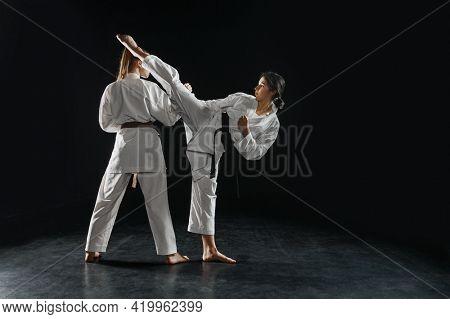 Two female karatekas in kimono, strike in action