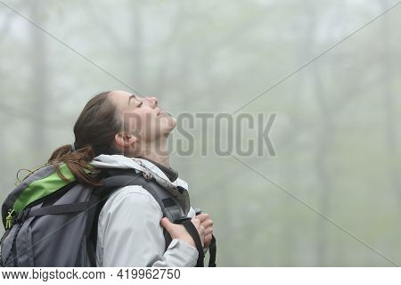 Side View Portrait Of A Happy Trekker Breathing Fresh Air In A Foggy Forest