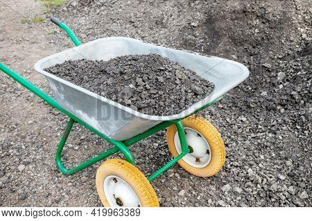 Hand Wheelbarrow With Gravel On The Street. As Part Of A Construction Project, A Man Is Transporting