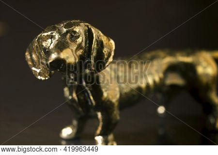 A Macro Close Up Shot Of A Dachshund Long Dog Bronze Figure Model Against Dark Background. Extreme S