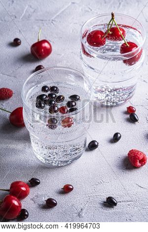 Fresh Cold Sparkling Water Drink With Cherry, Raspberry And Currant Berries In Two Transparent Glass