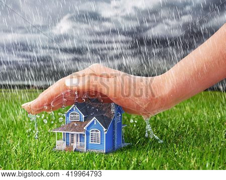 Save House. Hand Protecting House From Rain On A Overcast Weather Background.