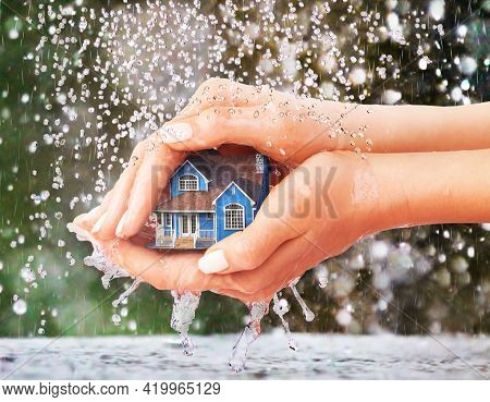 Save House. Hands Protecting House From Rain On A Blur Background.
