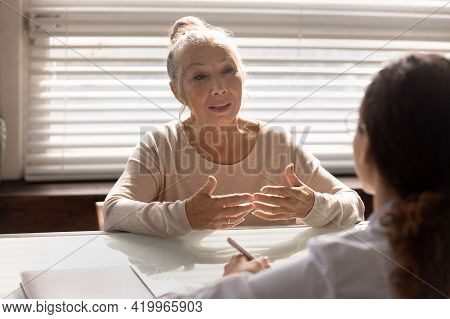 Aged Female Pensioner Patient Sit At Doctor Office Sharing Complaints