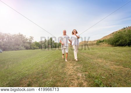 Seniors outdoors Adult man and woman in park Happy couple running barefoot