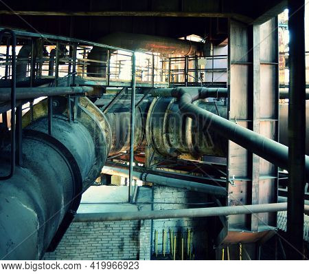 Old Abandoned Factory Interior With Many Rusty Piping. Big Rusty Piping In The Factory.