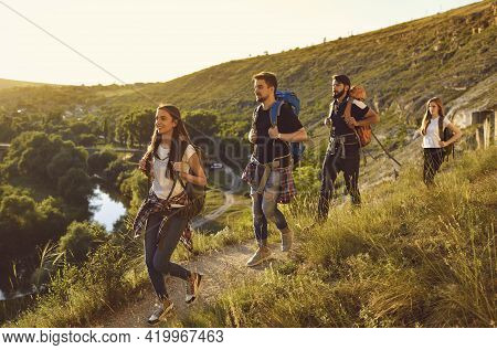 Group Of Smiling Tourists Hikers Hiking On Nature With Backpacks With Green Valley And River At Back