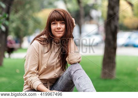 Portrait Of A Young Caucasian Woman Posing In A Park.