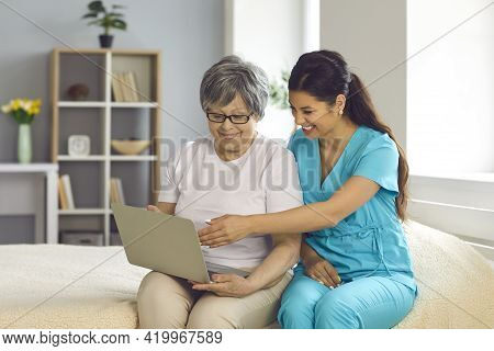 Friendly Home Care Nurse Teaching Happy Senior Woman To Use Modern Laptop Computer