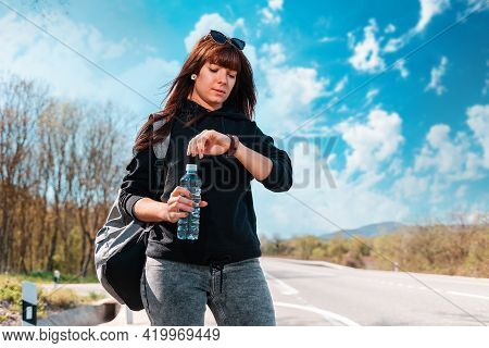 A Young Waiting Caucasian Woman Looks At Her Wristwatch. Countryside Road On The Background. The Con