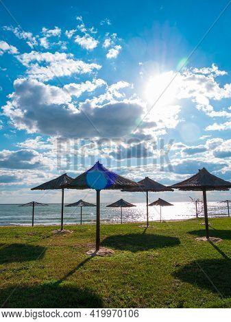Straw Umbrellas On Green Grass Harsh Shadow, Sand Beach Vivid Blue Sea Water Sky Background Sunbeam.