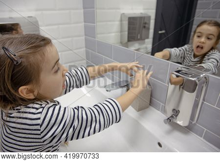 Little Girl Uses Liquid Soap To Wash Her Hands. Hygiene And Cleanliness In A Coronavirus Environment